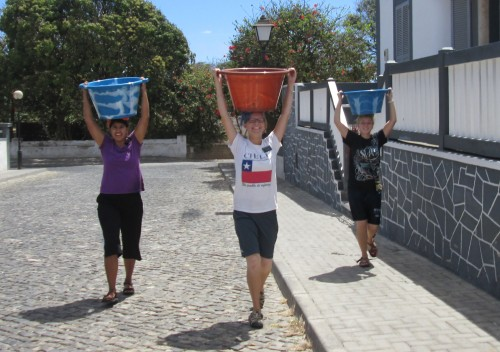 Sister missionaries carrying buckets of water